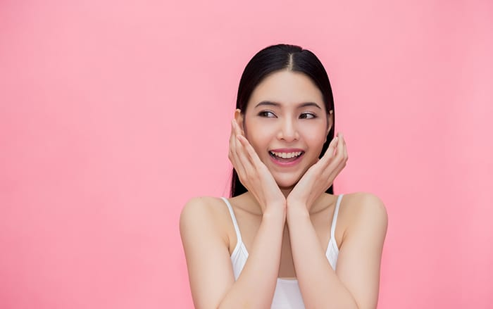 Excited and surprised smiling Asian 20s woman isolated over